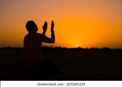 Silhouette of young muslim man praying on sunset,Ramadan festival concept