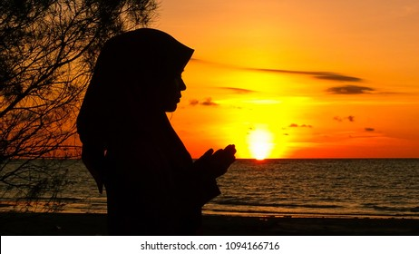 Silhouette of young muslim woman with hands raised,praying to the god near the sea on a beach at sunset.Copy space inspiration conceptual.