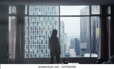 Silhouette of young pensive woman stands by the big window and looking out her apartment on the city buildings