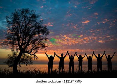 silhouette of young peoples in outdoor. Hands up.