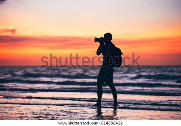 Silhouette of the young photographer. Photo shooting during amazing sunset on the tropical beach.