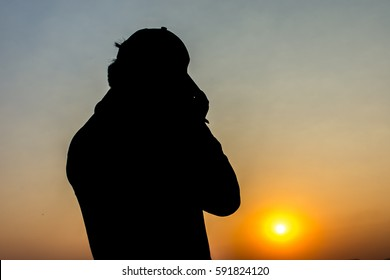 Silhouette of young photographer at sunrise