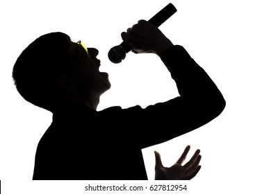 Silhouette of a young pop music artist in glasses singing emotionally into a microphone in a suit on an isolated white background