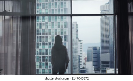 Silhouette of young pretty woman stands by the big window and looking out her apartment on the city buildings