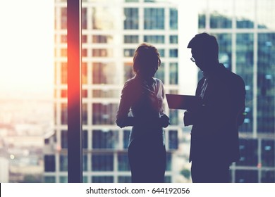 Silhouette of young purposeful two business partners working on digital tablet while standing near skyscraper office window,man and woman professional bankers using touch pad for teamwork during break