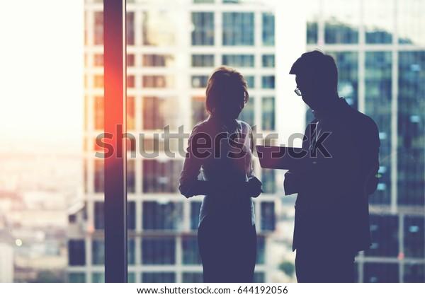 高層ビルオフィスの窓の近くに立ちながらデジタルタブレットで作業を行う若い目的に合った2人のビジネスパートナー、休憩時にタッチパッドを使った男性と女性のプロの銀行家のシルエット