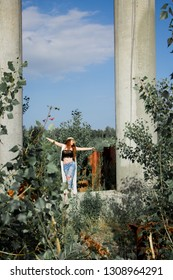 Silhouette of young redhead girl in hat and jeans near the old stone column