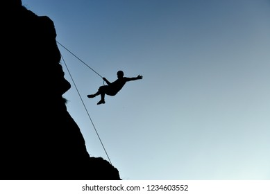 silhouette of young rock climber