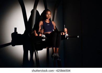 Silhouette of young sexy african-american woman fitness instructor working out at the gym