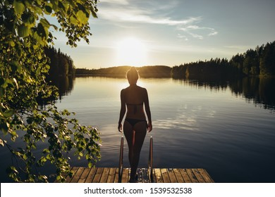 Silhouette of young shapely woman in bikini stand at pier after sauna. Summer evening sunset on the lake in Finland. Calm finnish nature.