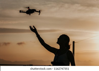 Silhouette of a young smiling woman landing a drone on her hand by the seaside, piloting with remote controller, sunset in the background