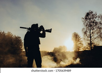 silhouette of a young soldier with a machine gun at sunset