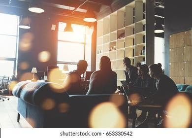 Silhouette of young startup team. Meeting on the couch. Big open space office. Five people. Intentional sun glare and lens flares