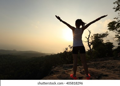silhouette of young successful woman open arms on sunset mountain peak