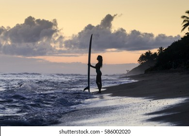 Silhouette of young surfer girl standing on the beach and watching the ocean and sunrise.