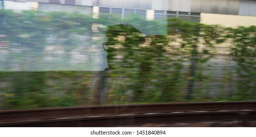 Silhouette of young unrecognizable man passenger reflected in the train window with green landscape passing by. Ecologic transport, environment sustainability, eco planet save earth creative concepts.