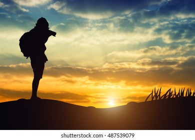 Silhouette of a young who like to travel and photography, taking pictures of the beautiful moments during the sunset ,sunrise.