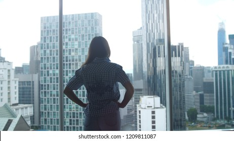Silhouette of young woman admires city view from the window in office.