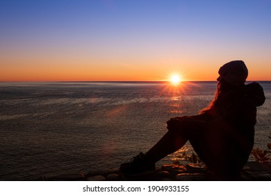 Silhouette of a young woman admiring the sunrise at Cap Bon-Ami, in the Forillon national park, Canada