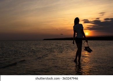 Silhouette of a young woman against a sea sunset