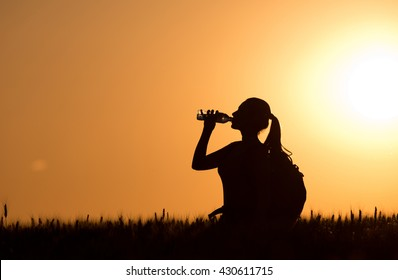 Silhouette of young woman with backpack drinking water from bottle in wheat field at sunset in summertime