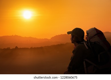 Silhouette of Young Woman Backpack sitting and looking to sunset time on the mountain hill. Backpacker in the summer concept.