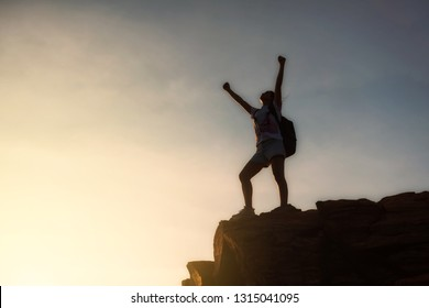 Silhouette young woman backpacker in victory pose with raised up arms on top of Mountain summit during sunset with copy space for text.