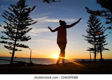 Silhouette of a young woman balancing on a slackline in the open air between two trees at sunset at scarborough beach in Perth, Australia.