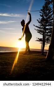 Silhouette of a young woman balancing on a slackline in the open air next to a tree at sunset at scarborough beach in Perth, Australia.  Perth, WA, Australia 27/05/2017