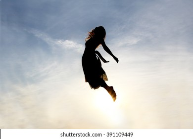 Silhouette Of A Young Woman Being Raised Into The Cloudy Sky Background As If