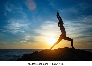 Silhouette of young woman doing exercises on the sea beach during sunset. Yoga, fitness and a healthy lifestyle.