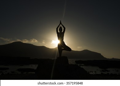 silhouette of a young woman doing tree yoga pose in the sunset