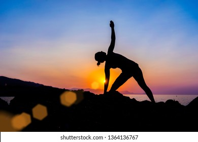 Silhouette of a young woman doing yoga on the beach at sunset.
