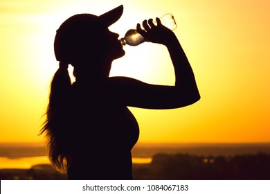 silhouette of a young woman drinking water from a bottle after physical exercise in nature, sports female profile in a cap on the field at sunset, concept of sport and relaxation