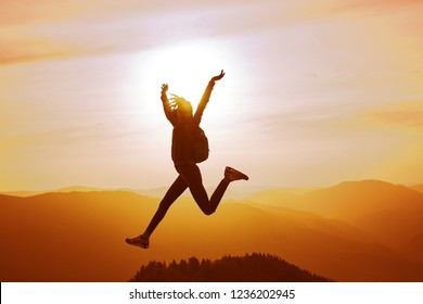 silhouette of Young woman enjoying life and jumping on mountain against orange sunset sky and mountains background