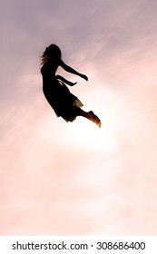 Silhouette of a young woman falling head-first through the sky at sunset.