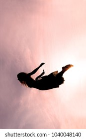 Silhouette of a young woman Falling through the pink sky.