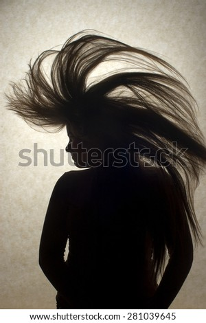 A silhouette of a young woman flipping her long hair