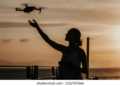 Silhouette of a young woman flying and landing a drone on her hand by the seaside, piloting with remote controller, sunset in the background