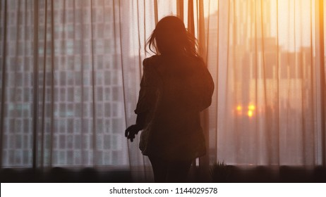 Silhouette of young woman goingto open curtains on building on the background in the window