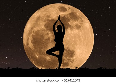 Silhouette young woman with good shape practicing yoga under full moon at night with stars