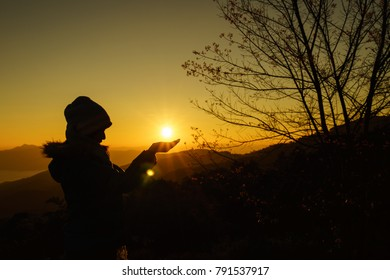Silhouette of young woman and hand holding the sun