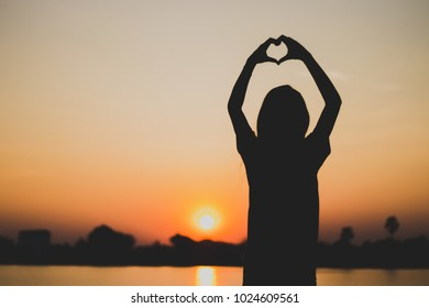 Silhouette of young woman hand made heart in summer sunset sky outdoor. People freedom style.
