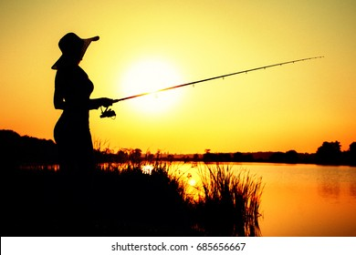Silhouette of a young woman in a hat engaged in sport fishing on the riverbank at dawn in the picturesque nature
