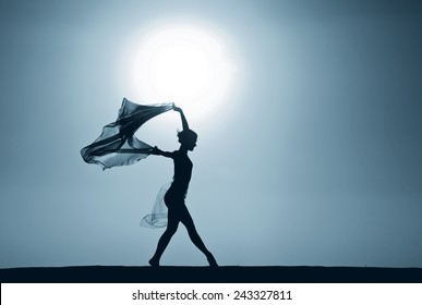 Silhouette of a young woman holding a billowing shawl in the wind at sunset