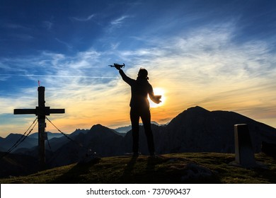 Silhouette of a young woman holding a drone, sunrise in the mountains