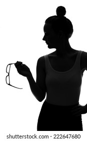 Silhouette of young woman holding spectacles against white background