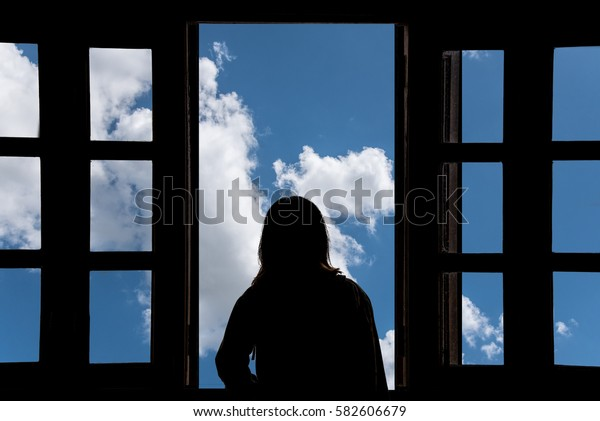 Silhouette young woman in the hotel, looking blue sky through the window