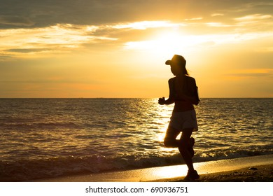 The silhouette of a young woman jogging at the beach on the background overlooking the sea and the light of the falling sun.