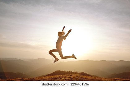 silhouette of Young woman jumping and enjoying life on mountain on sunset sky and mountains background